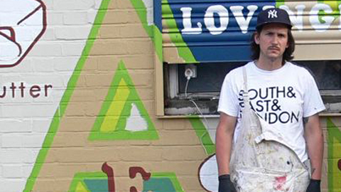 Matthew McGuinness in front of the Sem Cafe mural. Pic: David Western