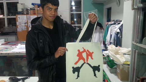 Ibrahim holding a bag he printed and stitched in the workshop. Pic: Samuel Johnston