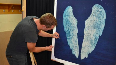 Chris Martin signing art work. Pic: Coldplay