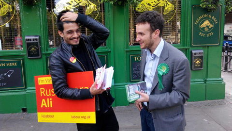 Labour campaigner Sadiq Islam (left) and the Green Party's Daniel Lee exchange pleasantries while talking to voters outside Bethnal Green station in Tower Hamlets. Pic: Arnau Busquets-Guardia