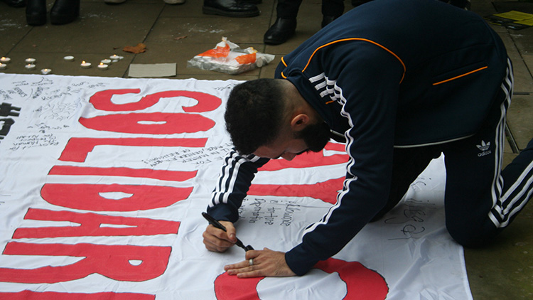 Students sign the banner. Pic Amalia Illgner