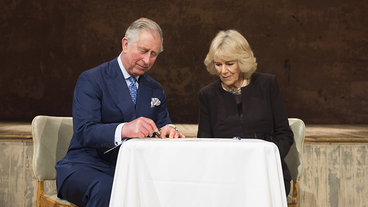 Prince Charles and Camilla sign the official opening document at Wilton's Music Hall. Pic: Matt Crossick