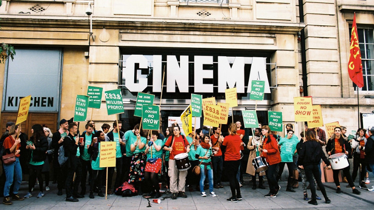 Hackney Picturehouse strikers stand in front of the cinema entrance