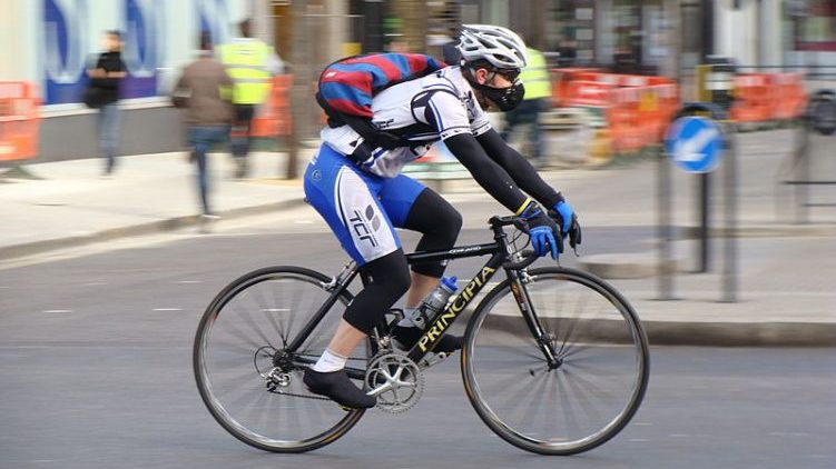 A cyclist wearing an air pollution mask.